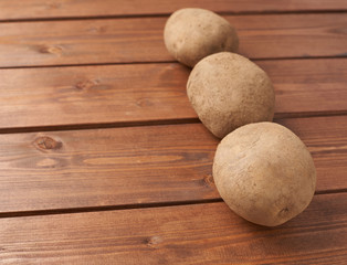Three potatoes over the wooden surface