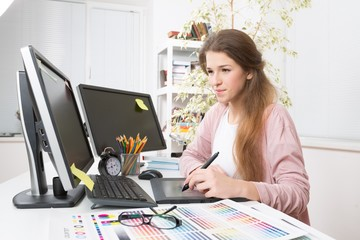 Adult. Side view of casual photo editors using graphics tablet