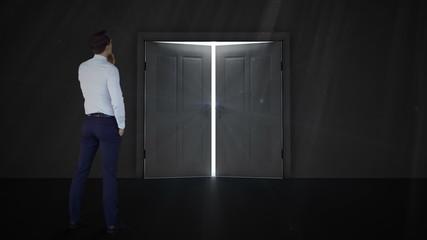 Businessman watching door open to light
