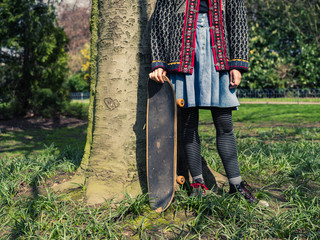 Young woman standing by tree with skateboard