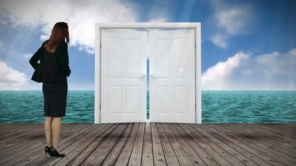 Door opening to ocean watched by businesswoman