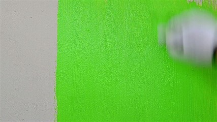 Close up man hand painting green color on the wall - Coloring gr
