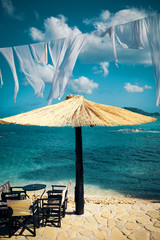Row of Straw umbrellas and lounges at  beach