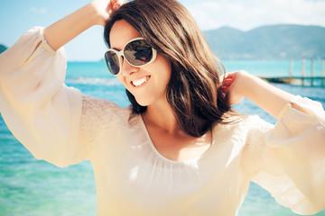 Happy woman in summer white dress on beach.