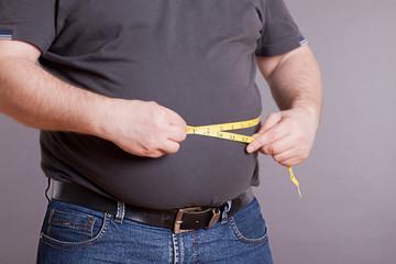 Mann mit Übergewicht, misst den Umpfang