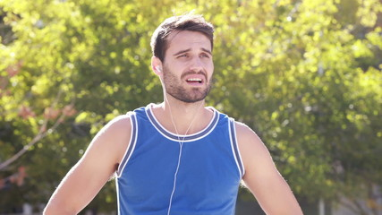 Happy jogger smiling at camera with thumbs up