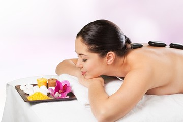 Rock. Picture of woman in spa salon with hot stones