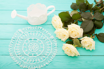 white roses, lace doily and watering can on wooden background
