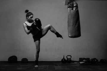 Young woman boxing workout in an old dark gym