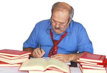 middle-aged man writing on the table filled with books