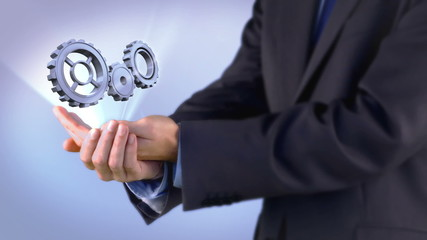 Businessman presenting cogs and wheels graphic