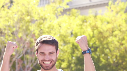 Euphoric jogger smiling at camera with thumbs up