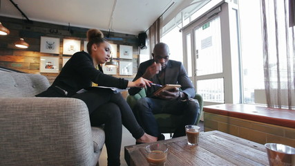 Two young business people sitting in a cafe discussing work