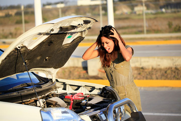 desperate woman in front of her open engine hood