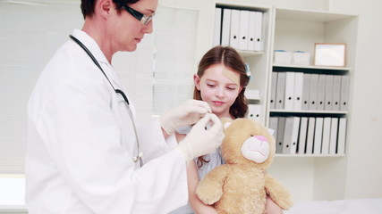 Doctor examining a teddy bear