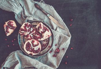 Red ripe peeled pomegranate on rustic metal plate and beige