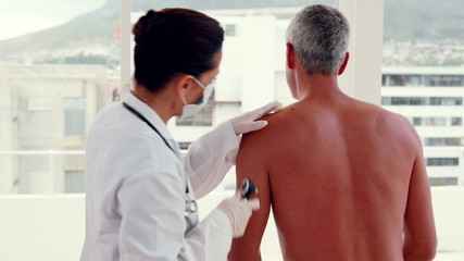 Doctor examining spot at her patient