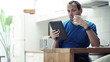 Man reading news on tablet computer and drinking coffee