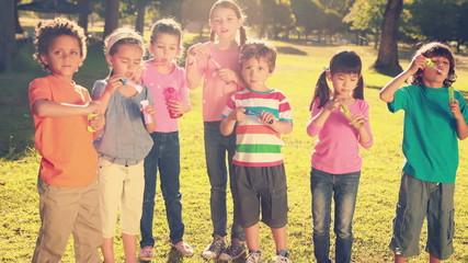 Little friends blowing bubbles in park