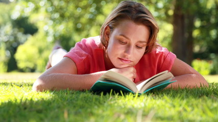Pretty woman reading book in the park