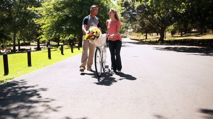 Happy couple walking with bike and bunch of flowers