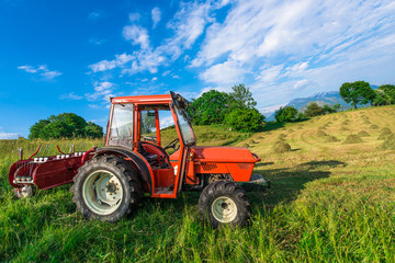 Red tractor in a mountain meadow with hay bales handmade
