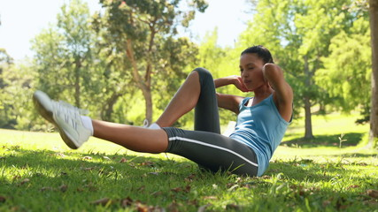 Fit woman doing sit ups in the park