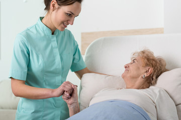 Supportive nurse with old lady