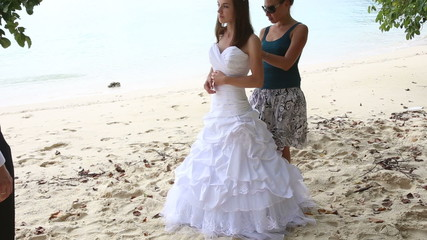 assistant helps bride tie corset of wedding dress on beach