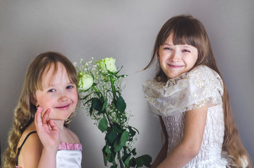 Girls are holding flowers and smiling