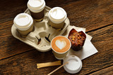 Paper cups of coffee latte and cake on wooden background