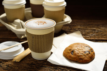 Paper cups of coffee and cookie on wooden background