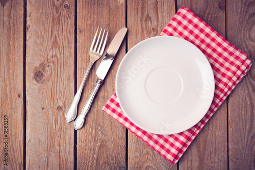Empty plate on tablecloth on wooden table. View from above - 81588259