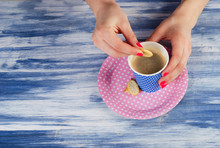 woman hands holding cup of coffee and cookies.