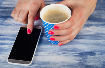 woman hand holding cup of hot coffee and using smartphone