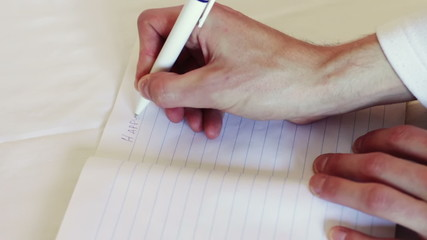 Man writes a pen in a notebook. The phrase I love you.