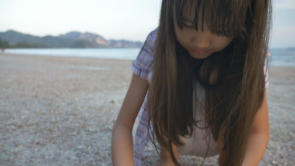 Little Asian child picking shells on the beach