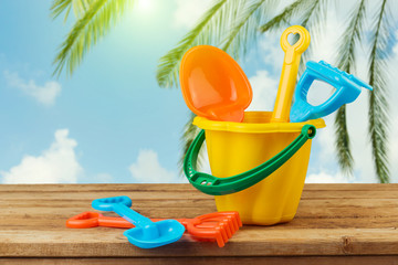 Children bucket and spade on wooden table over palm tree