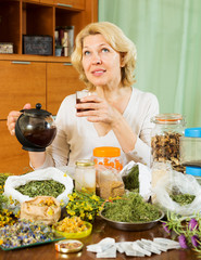 mature woman with dried herbs brewing herbal tea