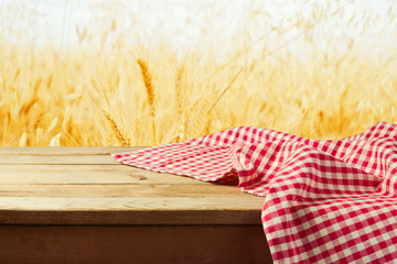 Red checked tablecloth on wooden deck over wheat field