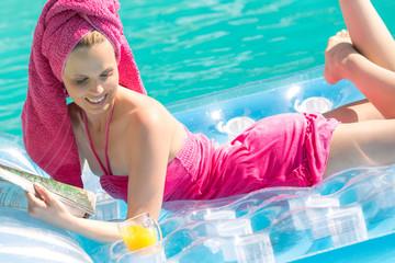 Hübsches Mädchen räkelt sich auf Luftmatratze im Pool