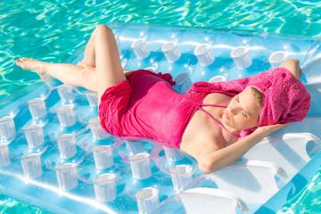 Mädchen auf Luftmatratze im Pool