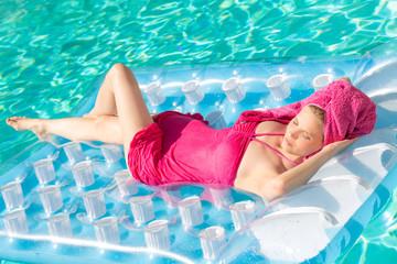 Hübsches Mädchen auf Luftmatratze im Pool