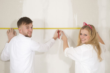 Happy young couple doing a odd-job in their new house