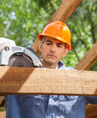Construction Worker Using Electric Saw On Timber Frame