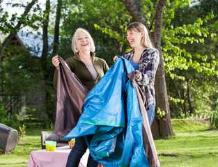 Cheerful Mother And Daughter Assembling Tent In Park