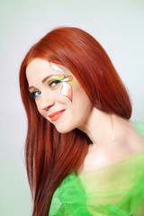 Portrait of beautiful red-haired girl with flower on face