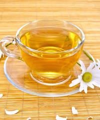 Herbal tea with camomiles on bamboo napkin