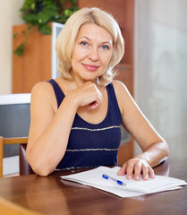 mature woman signing documents