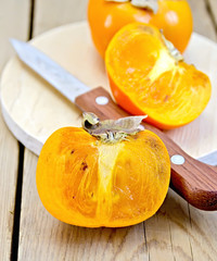 Persimmon with knife on board